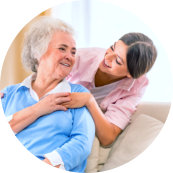 senior woman and caregiver smiling to each other